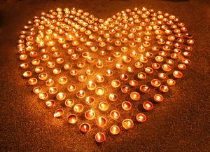 Love heart shape made out of burning candles and light