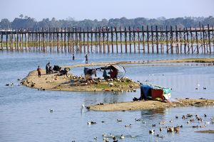 People crossing the U Bein Bridge across the Taungthaman Lake in Amarapura, Mandalay