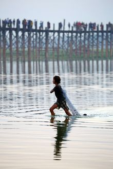 The U Bein Bridge with a fisherman walking across the Taungthaman Lake in Amarapura