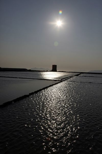 Silhouette of disused windmill at sunset with light relflected in the water in the Salt Pans in Trapani, Sicily, Italy
