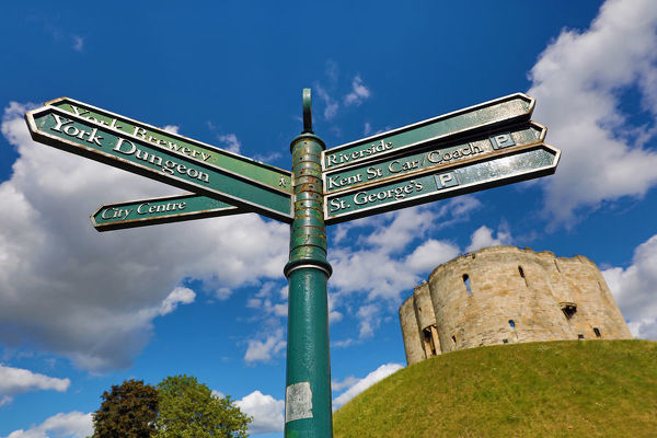 Tourist information signpost and Clifford's Tower at York Castle in York, Yorkshire, England