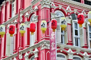 Chinese lanterns hanging in front of colourful buildings with shutters and windows