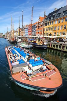 Coloured houses and a tourist sightseeing tour boat at Nyhavn Quay in Copenhagen, Denmark