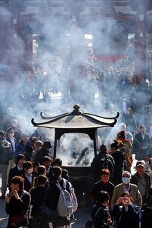 Crowds of people burning incense at the Shinto Shrine at Senso-Ji Bhuddist Temple