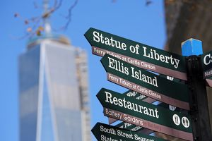 Direction signs to the Statue of Liberty and Ellis Island with One Trade Center