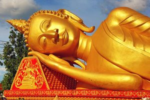 Giant gold reclining sleeping Buddha statue near Wat That Luang Temple, Vientiane, Laos