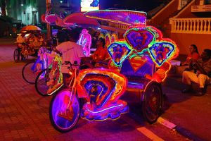 Illuminated decorated kitsch cycle trishaw rickshaw with soft toys at night in Malacca
