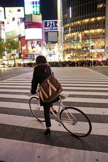 Japanese street scene showing crowds of people crossing the street and a cyclist