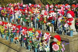 Jizo statues and pinwheel windmill toys in the Zojoji Temple cemetery garden in Tokyo