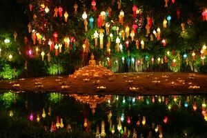 Lanterns and candles reflected in a pool with a Buddha stature for the Loy Krathong