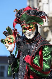 Man wearing a jester mask and costume at the Venice Carnival