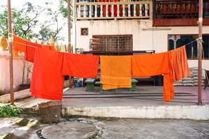 Orange Buddhist Monk clothes and robes on a washing line, Vientiane, Laos