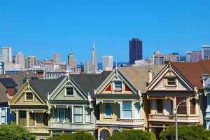Painted Ladies Victorian houses near Alamo Square and city skyline, San Franciso