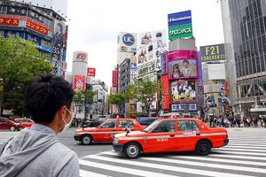 Pedestrian crossing and street scene with Japanese taxi cabs in Shibuya, Tokyo, Japan