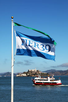 Pier 39 flag, sightseeing boat and Alcatraz prison island in San Franciso, California