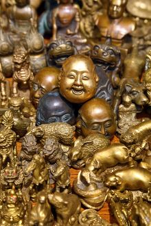 Pile of brass figures including laughing Buddha head in the Old City, Shanghai, China