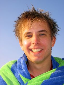 Portrait of a smiling man on summer holiday wrapped in a towel
