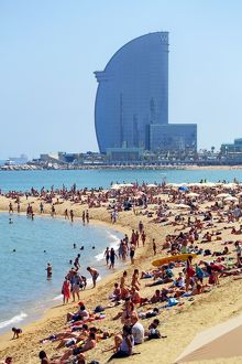 Scene of holiday crowds on the crowded beach and the W hotel, Barcelona, Spain