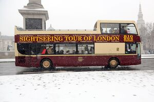 Snow and tourists on sightseeing bus in Trafalgar Square, London