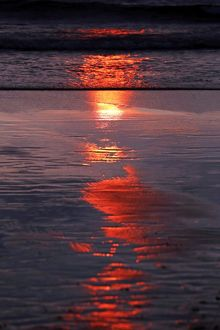 Sunset reflection on wet sand on Legian Beach, Denpasar, Bali, Indonesia