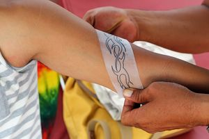 Tattoos for tourists. Temporary henna tattoo being applied, Legian Beach, Denpasar