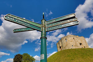 Tourist information signpost and Clifford's Tower at York Castle in York, Yorkshire