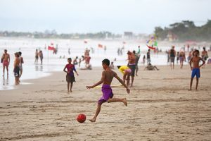Tourists on holiday playing football on Legian Beach, Denpasar, Bali, Indonesia