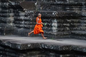 Young Buddhist monk running at Angkor Wat Temple, Cambodia